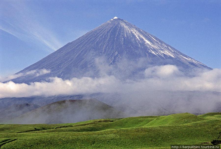 А здесь уже позднее утро. Солнце уже высоко, земля прогревается и вокруг горы образуется юбка из облаков.