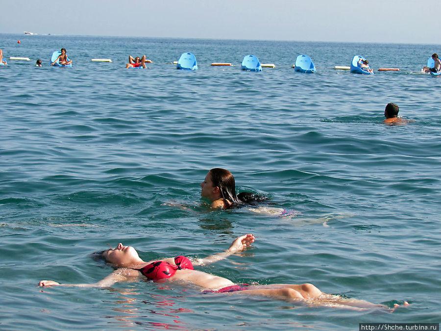 вдалеке очень интересные пластиковые лежаки на воде — только на нашем пляже