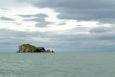 Одинокой скалой остров меряется силами со штормами и тучами, врос глубоко в водах залива