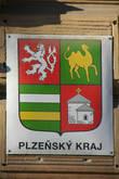 Герб и флаг Plzeňského kraje (Пльзеньского края)  Щитовое поле герба французского типа красное. Первое поле — Чешский, глядящий право коронованный серебряный лев в прыжке, на красном фоне, символ чешской государственности и положения региона в Чешской Республике, т.е. не в Моравии и Силезии. Второе поле — Золотой, шагающий влево двугорбый верблюд на зеленом заднем плане, является дериватом пльзеньского герба. Речь идет о его второй самой древней части. Герб города, распространил после 1433 года император Zikmund (Сигизмунд), намекая на эпизод из гуситских войн, когда жители города во время вылазки против войск, которые держали город в осаде, похитили верблюда, которого гуситы получили в подарок от польского короля.  Третье поле — Серебряное и золотое бревно на зеленом поле. Зеленый цвет символизирует лесистую границу — Šumava (Шумава) и Český les (Чешский Лес). Именно граница вместе с центром является наиболее важным «природным» знаком этого края. Расположение на границе с Германией находит свое отражение в истории края практически во всех эпохах — в средневековье здесь происходили сражения, и строились замки, до 1989 года здесь была непроходимая граница, которая персонифицировала весь край, а в настоящее время граница — а с ней снова и целый край – является, наоборот, символическими воротами в Европейский союз.  Два бревна символизируют две крупные реки, которые отводят воду из этого региона — серебряную Berounku (Бероунку), а золотое – золотоносную Otavu (Отаву). Бассейны этих рек охватывают весь регион.  Четвёртое поле — Серебряная ротонда на красном поле.  Поле ссылается на древнюю пльзеньскую ротонду Св. Петра, самое древнее из сохранившихся зданий в Чешской Республике. Это святилище было центральным храмом Staré Plzně (Старый Пльзень) — первого административного центра региона. На гербе это поле представляет богатую историю этого региона и его духовные традиции.