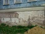 На доме нарисовано то, как он и улица выглядели 100 лет назад