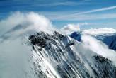Облака будто неторопясь перекатываются через вершины и скользят по склонам гор.