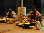 Рикши готовят ужин. Их подстилки и вещи днём всегда аккуратно сложены в углу здания.
