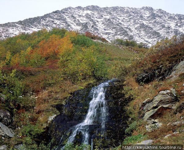 Водопад в долине реки Фейкошор. Если от Неройки на Парнук идти через истоки Щекурьи, озёра Паток и Кулик-Турское, то никак не миновать притока Маньи, под названием Фейкошор. Именно по его крутому распадку и придётся спускаться в долину Маньи. Этот водопад находится на одном из небольших ручьёв, впадающих в Фейкошор в его верховьях. Замечательная композиция из заснеженного скалистого гребня, травянистого склона в осенней раскраске и симпатичного водопада.