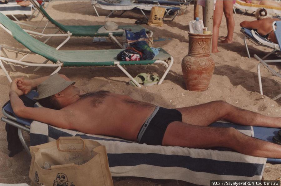 Лежаки на пляже и загорающий народ...