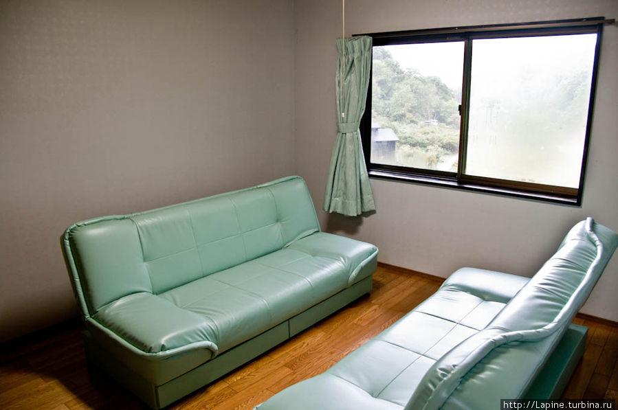 Не шибко-то уютная гостиная с кожаными диванами, вход в которую есть и из прихожей, и из кухни.