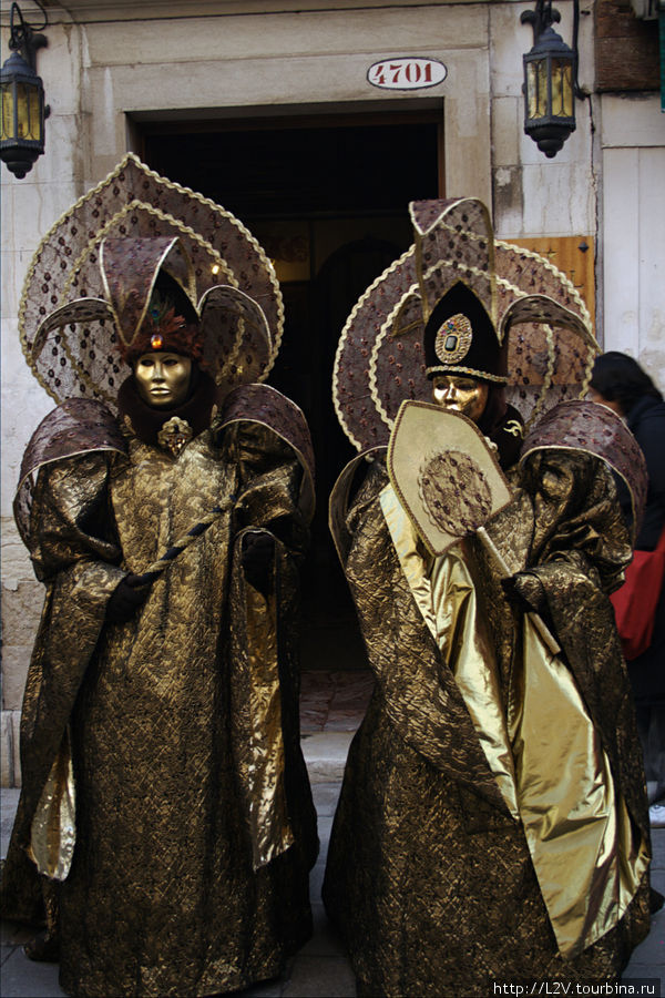 Маскеры в полных масках, дефилирующие по улочкам, фотающие друг друга и с туристами
