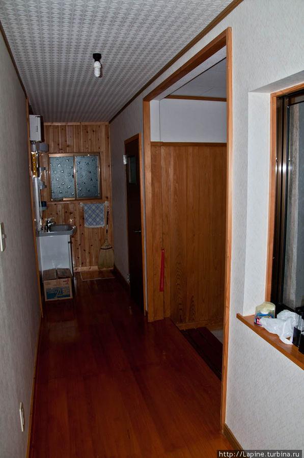 Прихожая со стороны входа во внутренние помещения: справа — выход наружу, за ним — дверь в сортир, в глубине — умывальник. Вода из-под крана — только холодная.