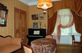 Центральное место в квартире занимает гостиная. Сотрудниками музея мастерски воссоздана атмосфера советской гостиной 20-30-х годов ХХ века с фотографиями на стенах, оклеенных цветными обоями.