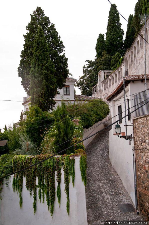 Алькубийя со стороны Альамбра Палас (виден угол ограды сада и вдали по центру здание, полуприкрытое высоким деревом — это и есть отель).