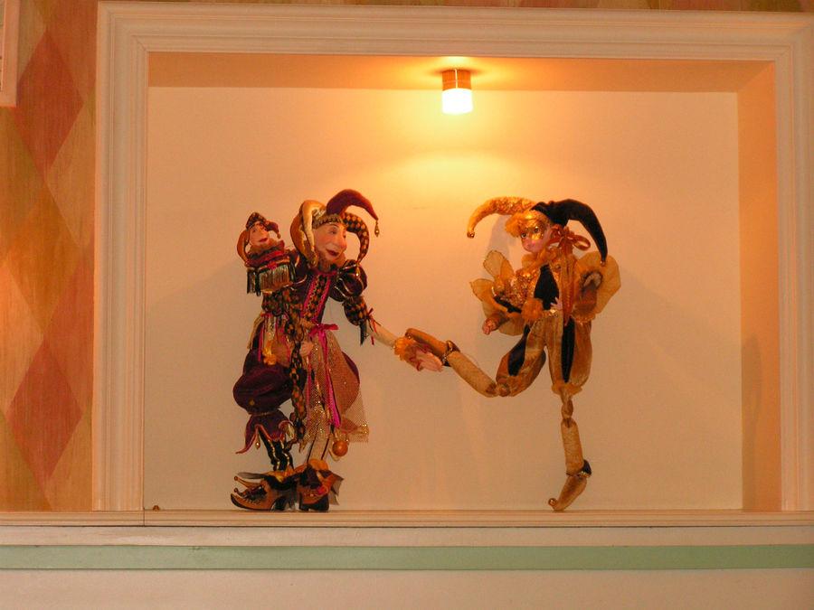 Куклы Арлекино украшают ниши в стене.