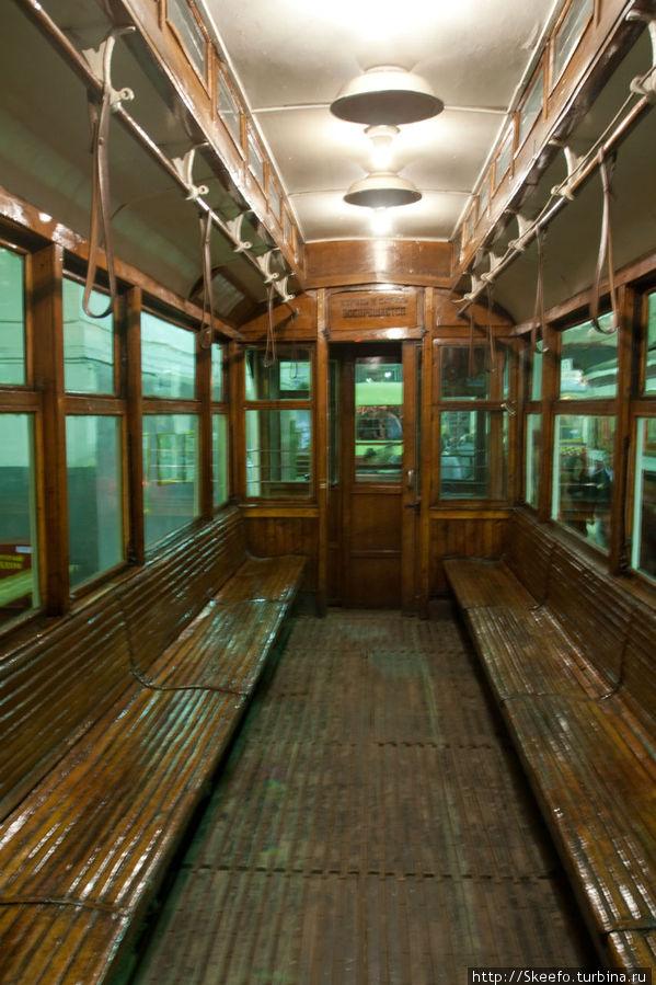 Это вагон одного из первых трамваев. Вверху дополнительные окна для освещения. Сейчас стоят яркие лампы, а когда-то были очень тусклые и без окошек было бы совсем темно. Кроме того эти вагоны, когда-то, делились на первый и второй класс. В первом классе зимой ставили ведра с углём, что бы было теплее. А на сиденьях были мягкие подкладки. Впрочем публика предпочитала ездить во втором, ведь если почти нет разницы (а так и было), то зачем платить больше?