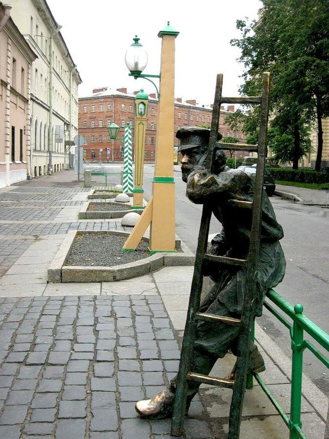С-Пб, Одесская улица. Вид сбоку на памятник фонарщику и часть фонарей.
