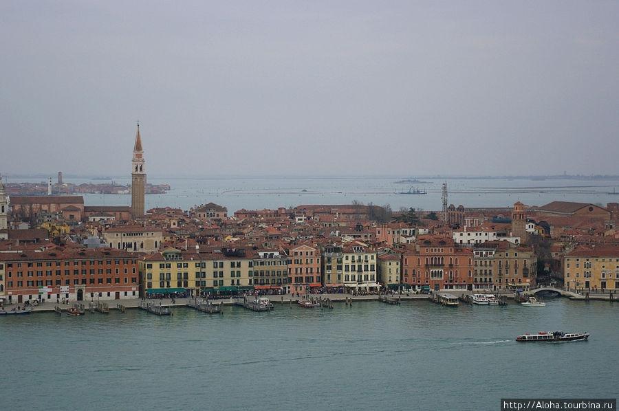 Красные черепичные крыши, палочки башен.
