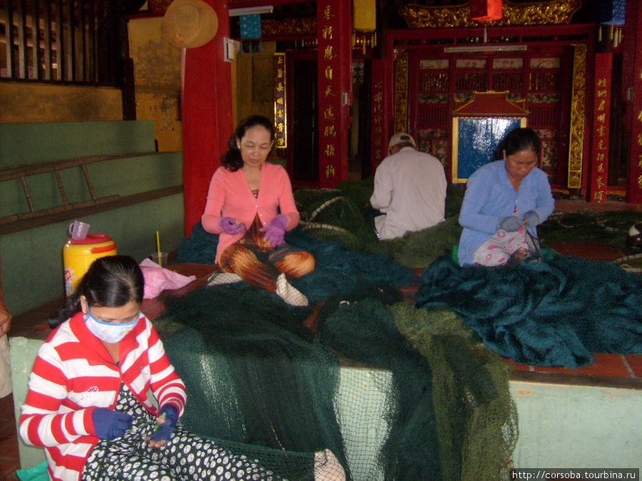 Женщины- рыбачки плетут в храме сети.