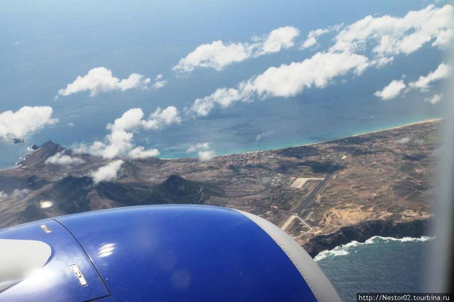 Остров Порту Санту на подлете к Мадейре. На дальнем берегу виден знаменитый многокилометровый песчаный пляж. Виден город Вила-Болейра и взлетная полоса.