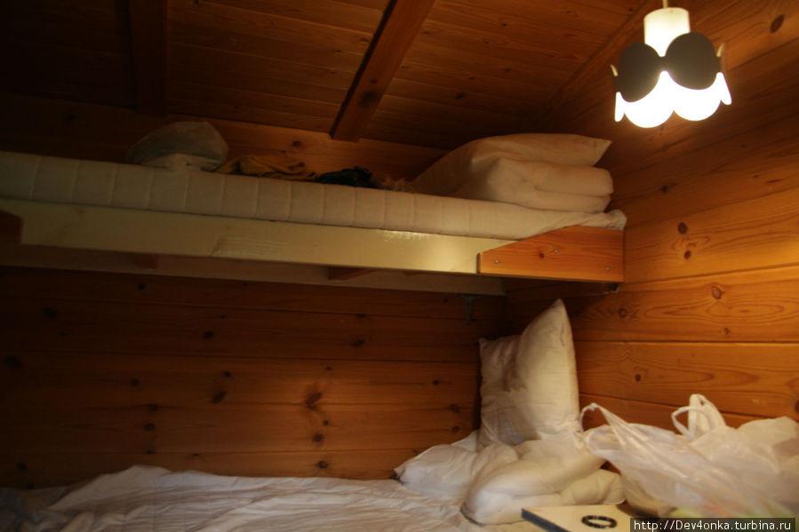Внутри домика стоят одинарная кровать и двухярусная.