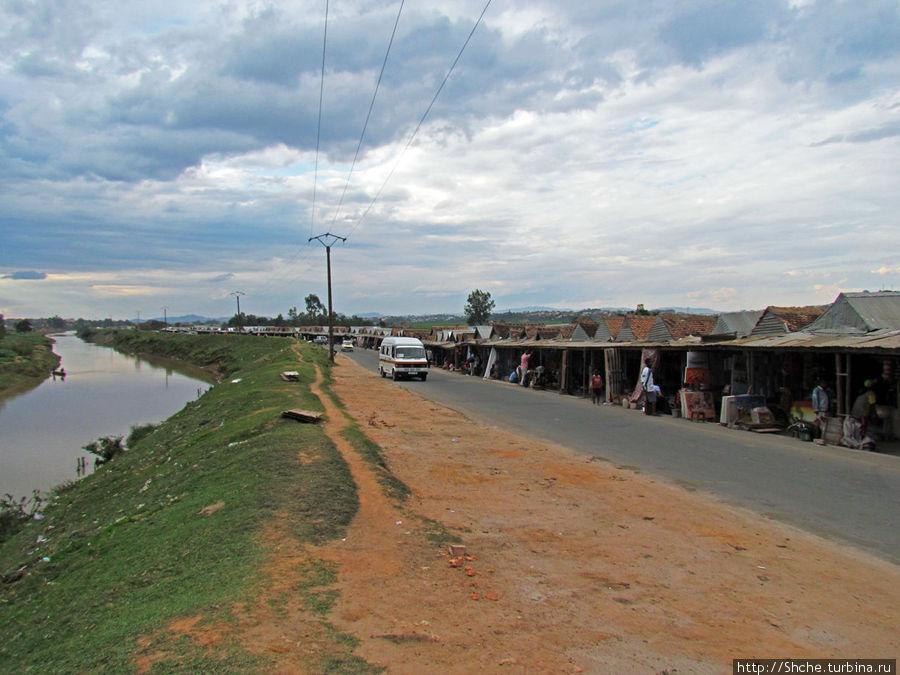Рынок расположился справа, от дороги, а слева течет река Ikora